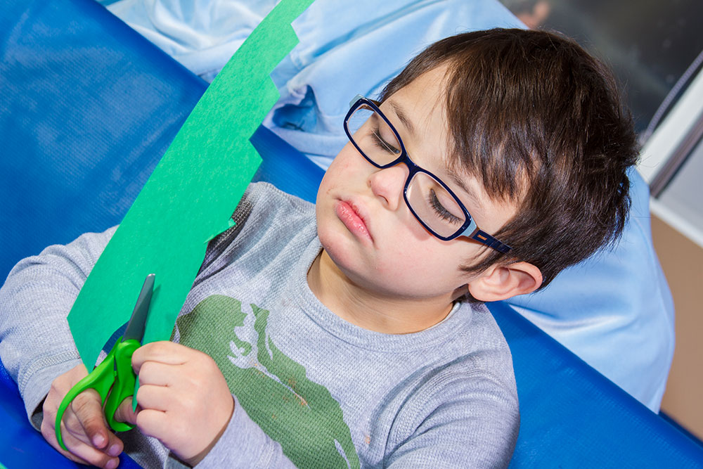 boy cutting paper with a scissors | Occupational Therapy