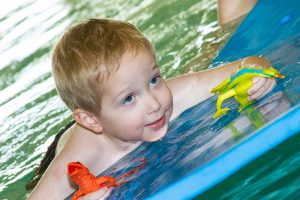 boy on a float in a swimming pool | aquatic therapy
