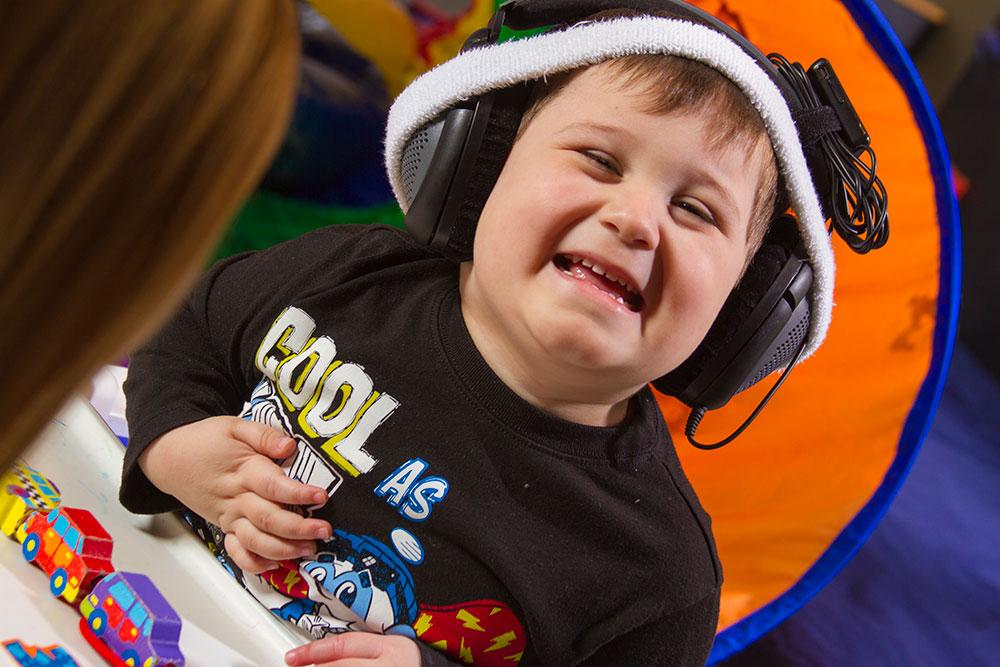 Little boy wearing headphones | speech therapy