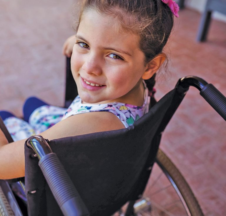 Girl in a wheelchair looking over her left shoulder | Careers in occupational therapy