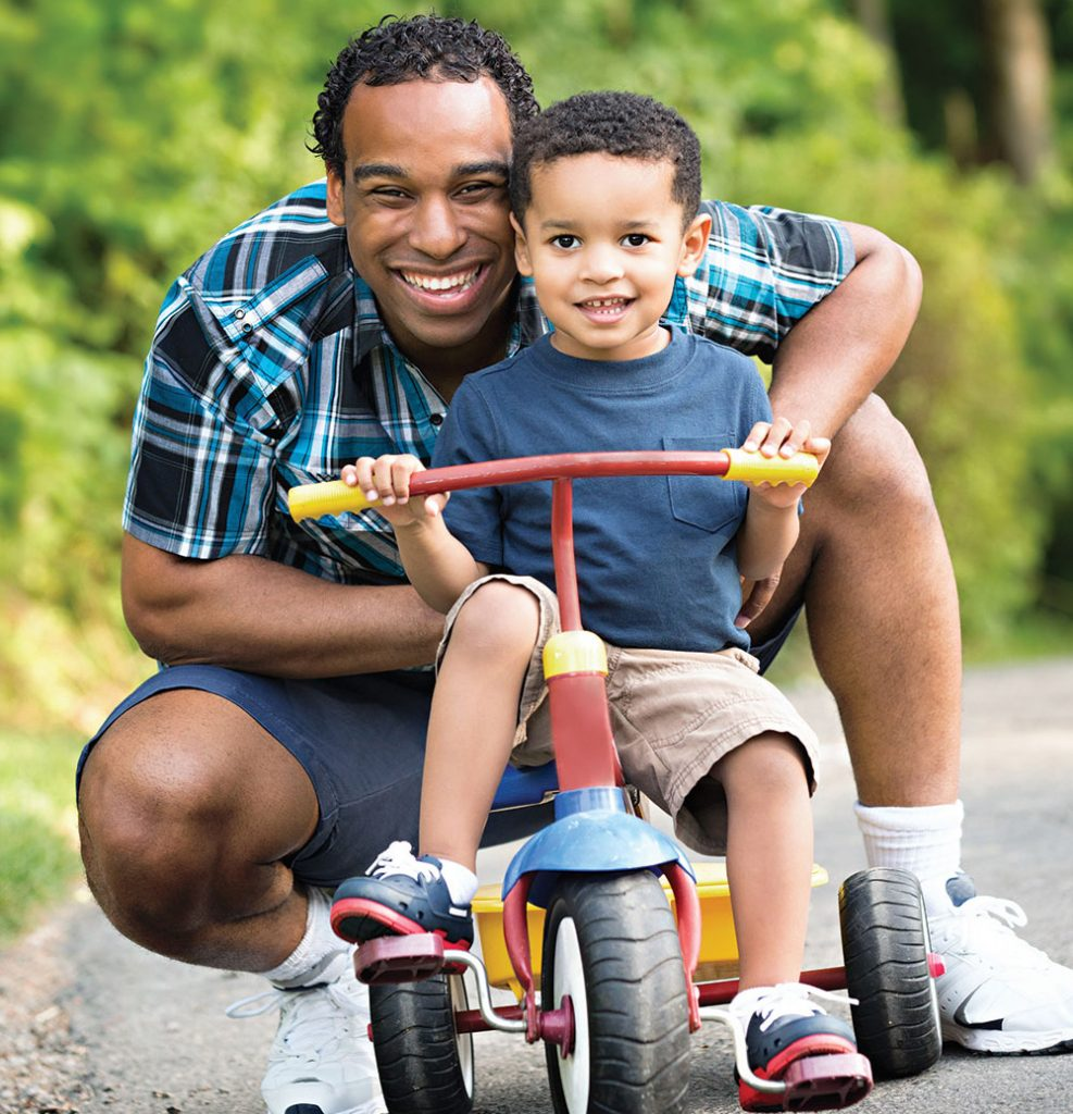 African American father and boy toddler (on a tricycle)