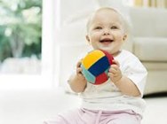 Baby sitting holding a multi colored ball | Infants playing with a soft ball can help improve motor skills.